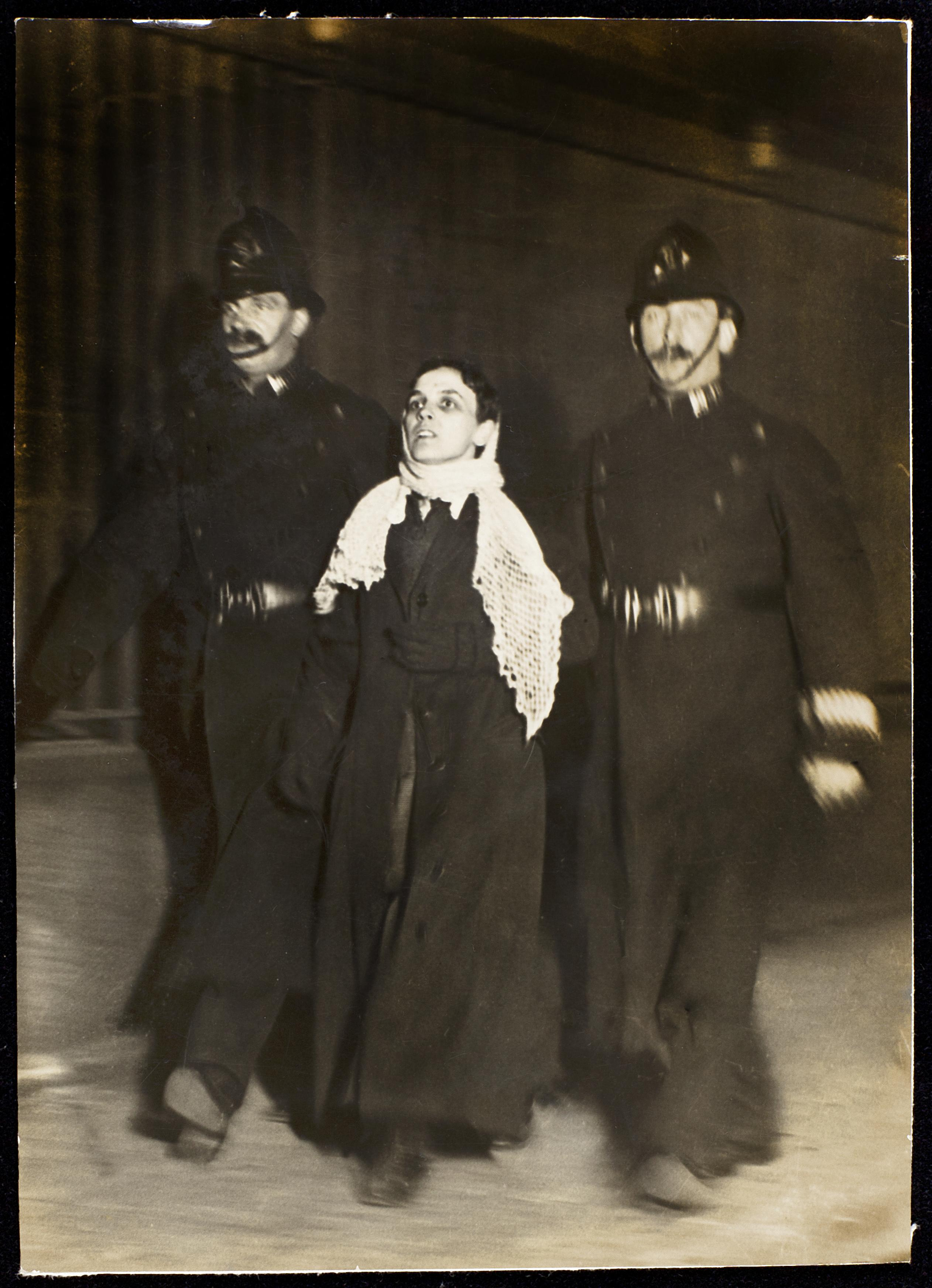 black and white photo of woman being led away by two policemen