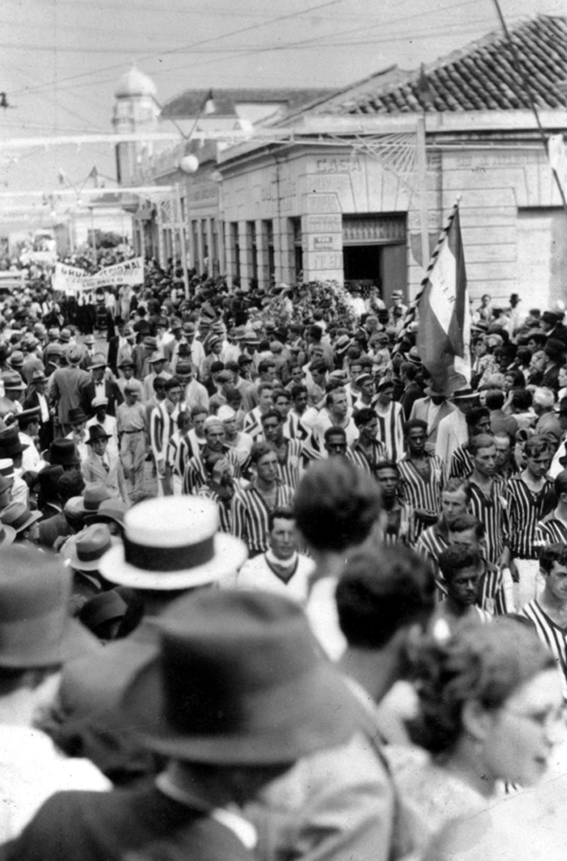 Fotografia em preto e branco da 1ª festa da uva de jundiaí, em 1934, com homens vestidos com roupas listradas, desfilando pelas ruas do centro, com uma multidão nas laterais.
