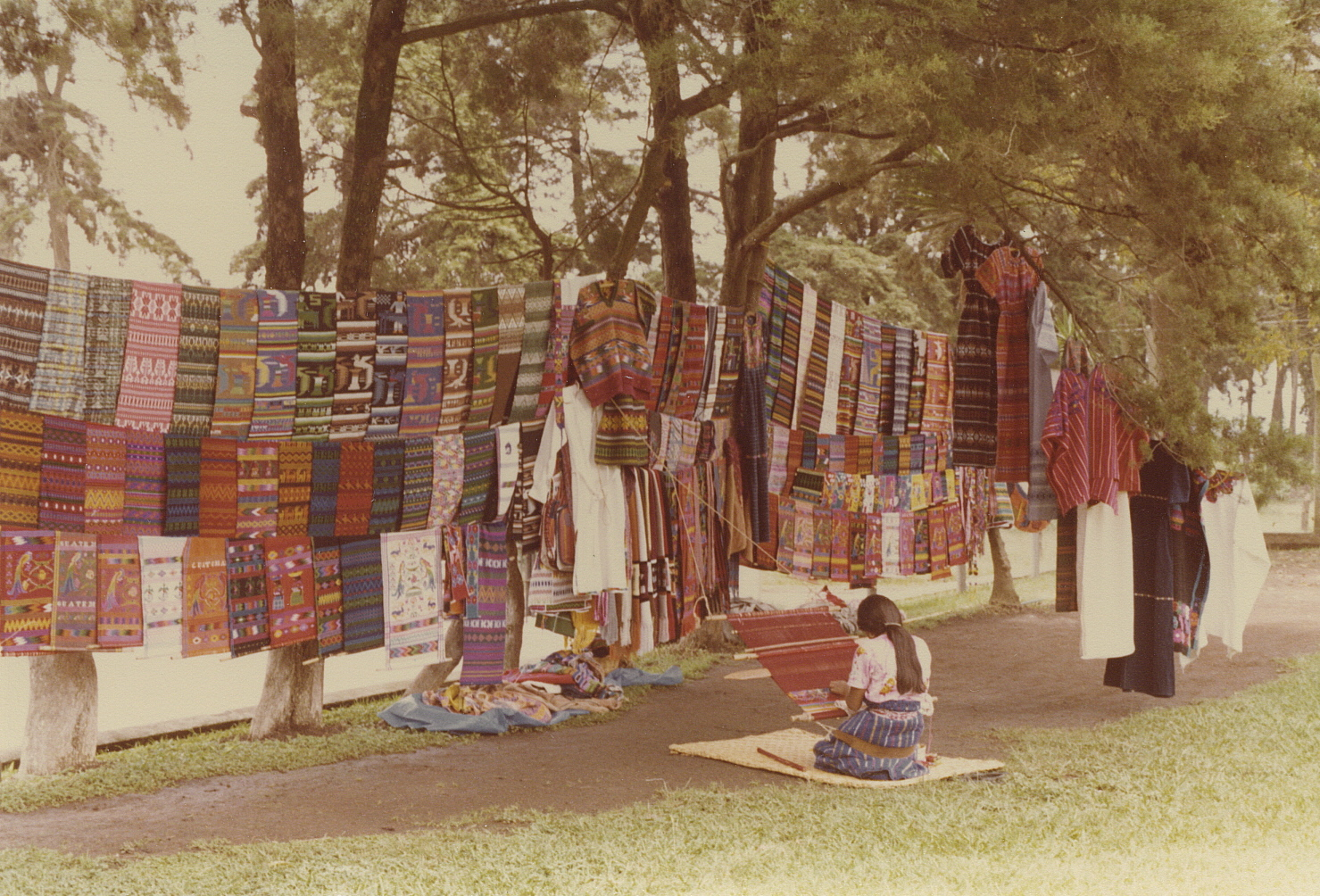 Brilliantly dyed traditional woven textiles of Guatemala, and woman weaving on a backstrap loom.