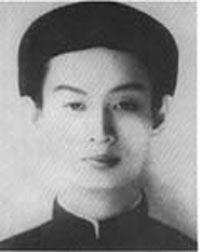 Młody, szczupły mężczyzna w wieku około 20 lat, z bystrymi oczami i nosem, ubrany w cylindryczny tradycyjny wietnamski nakrycie głowy i tunikę.  Zarówno nakrycie głowy, jak i tunika są czarne.