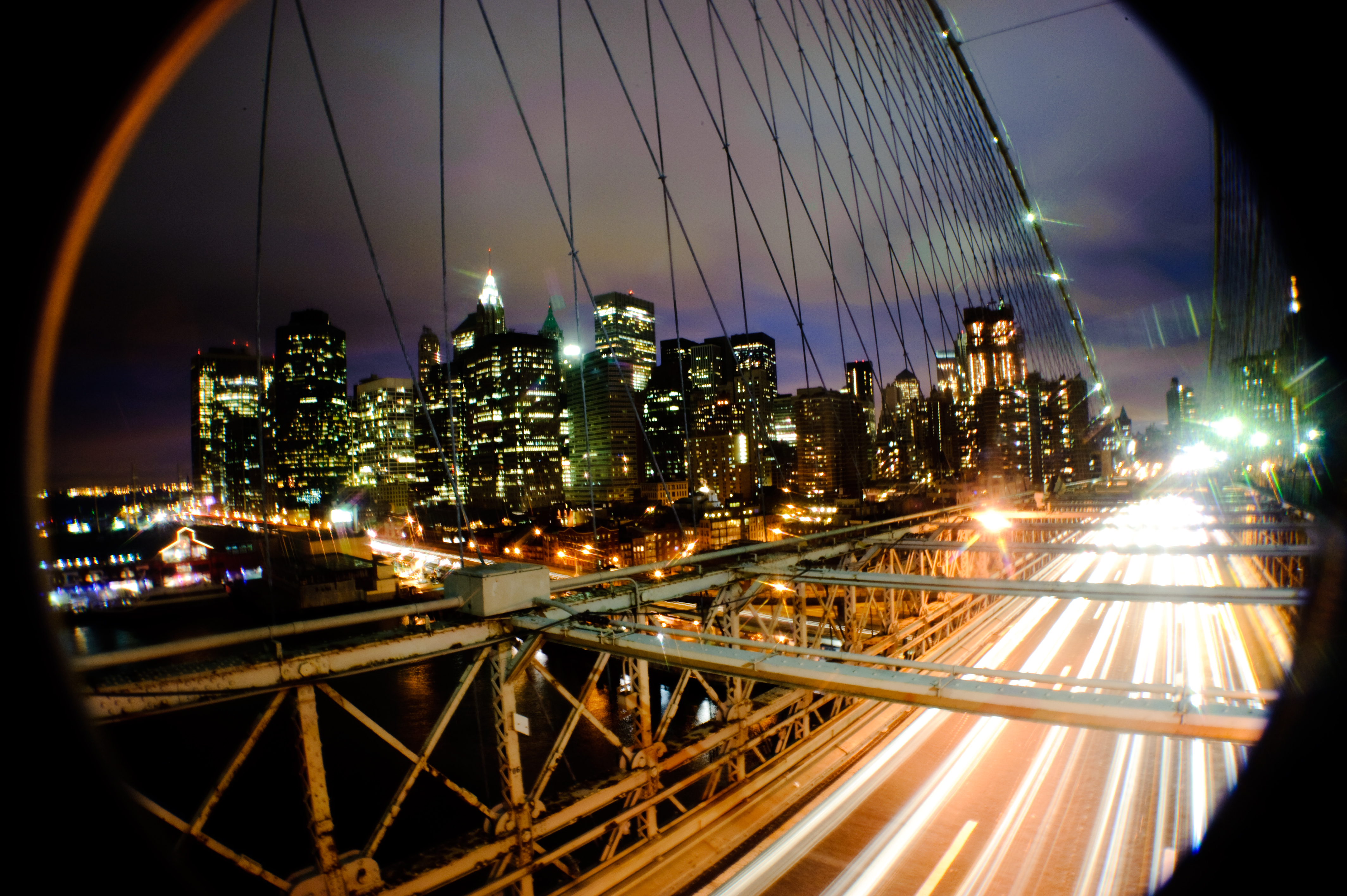 Description new york buildings seen from brooklyn bridge at night