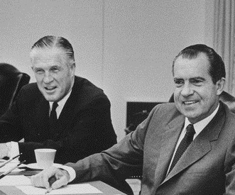 Photograph of Romney and Nixon, both looking at and grinning at something off-frame