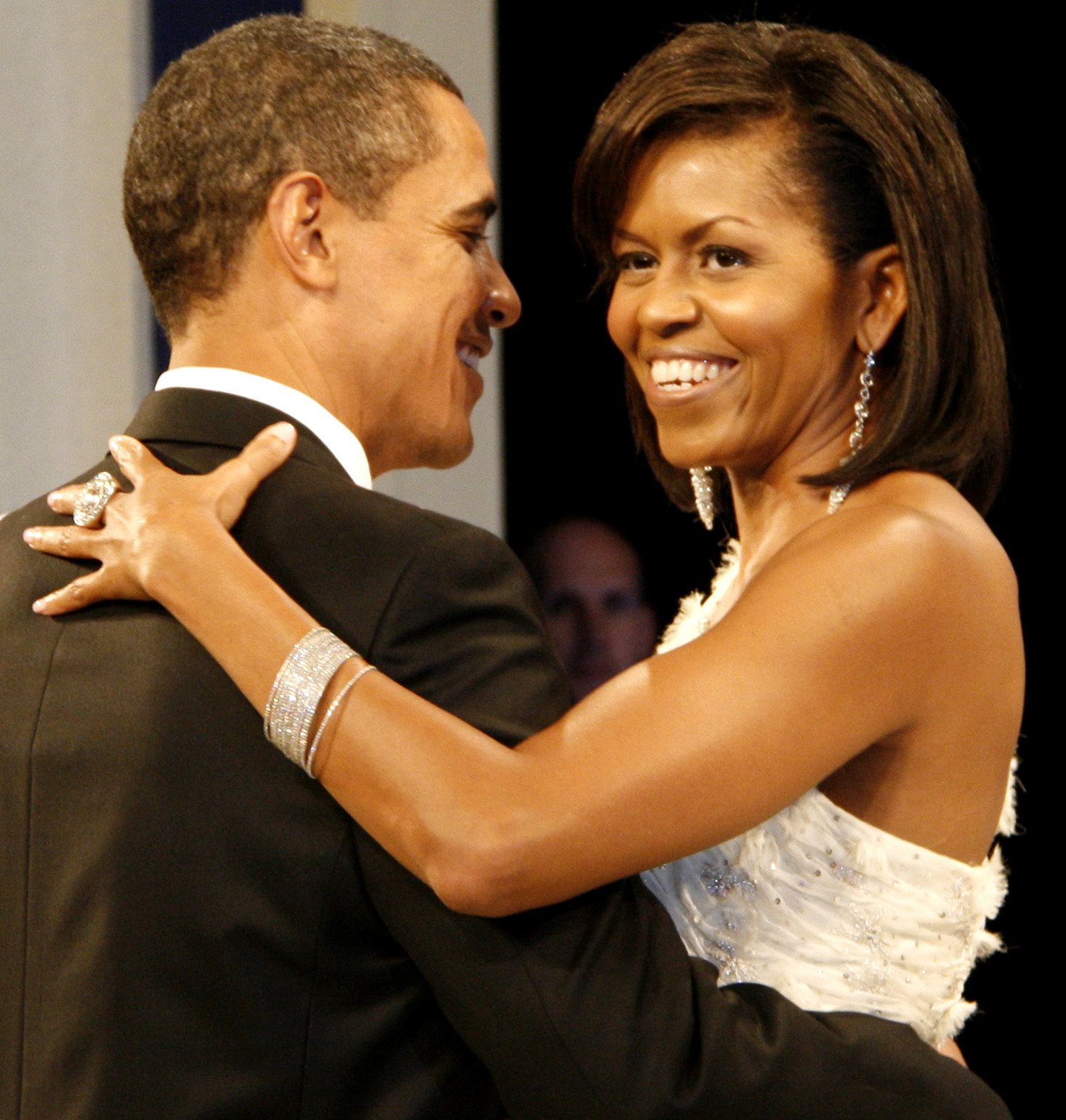 Barack and Michelle Obama dancing arm-in-arm and smiling. She is wearing a white dress, large ring, long earrings and a bracelet. He is wearing a black tuxedo.