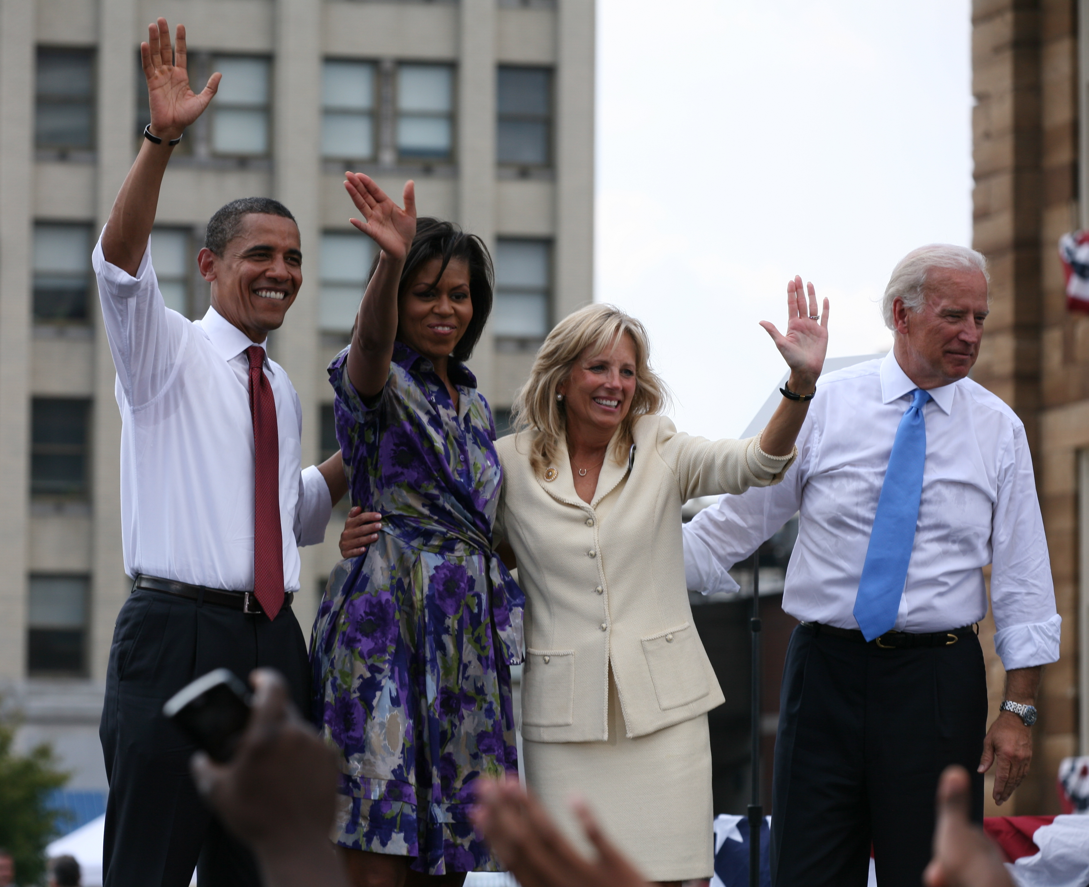 Barack And Michelle Obama And A Woman And A Man On An Outdoor Stage. The