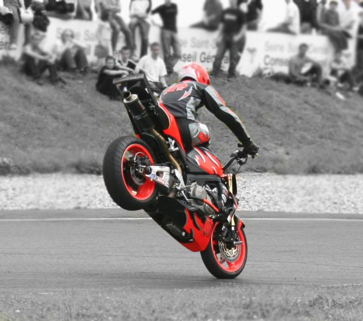 A motorcyclist performing a stoppie.
