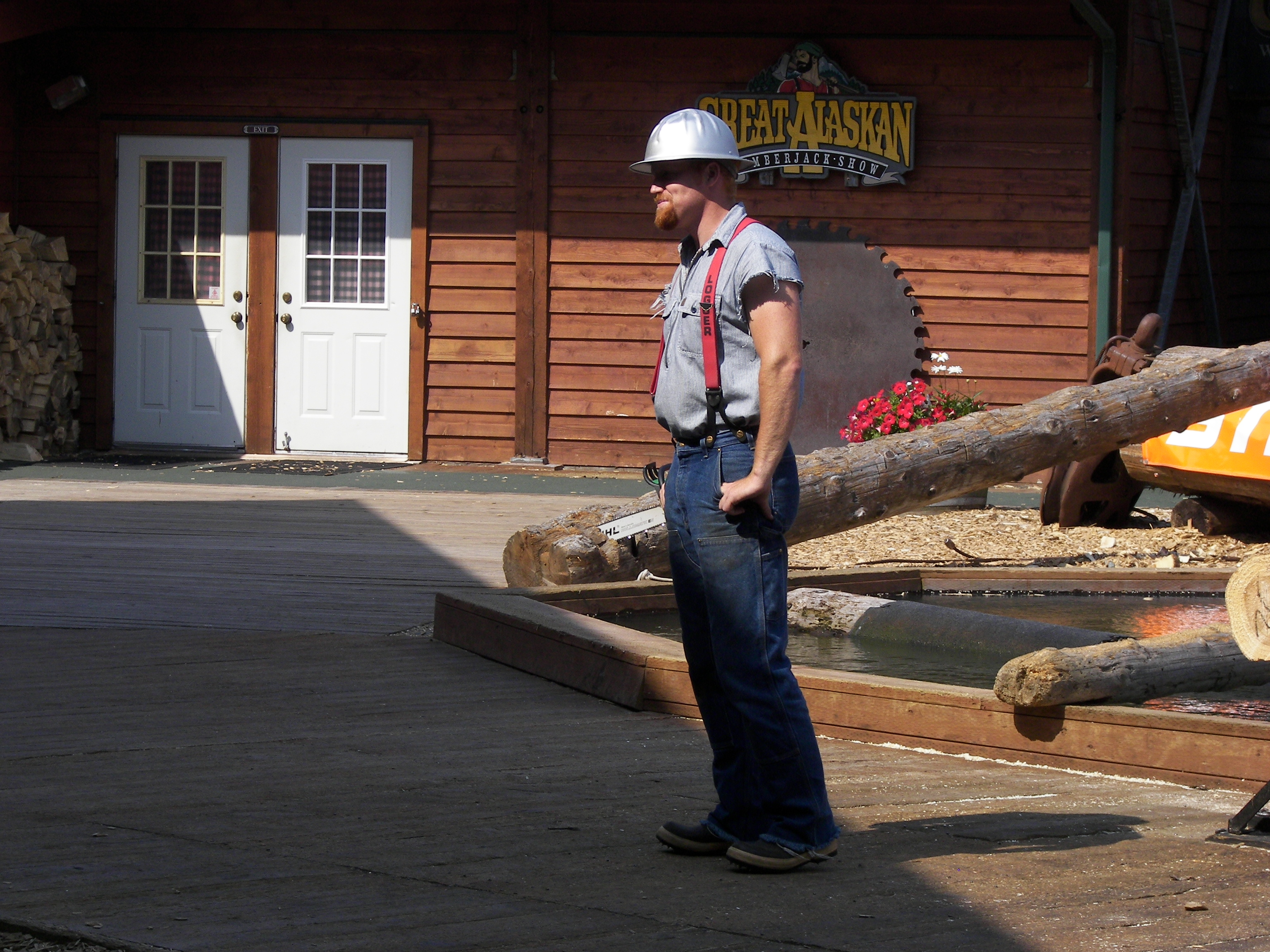 A logger in hard hard, jeans, and flannel shirt standing by a few logs and an office building