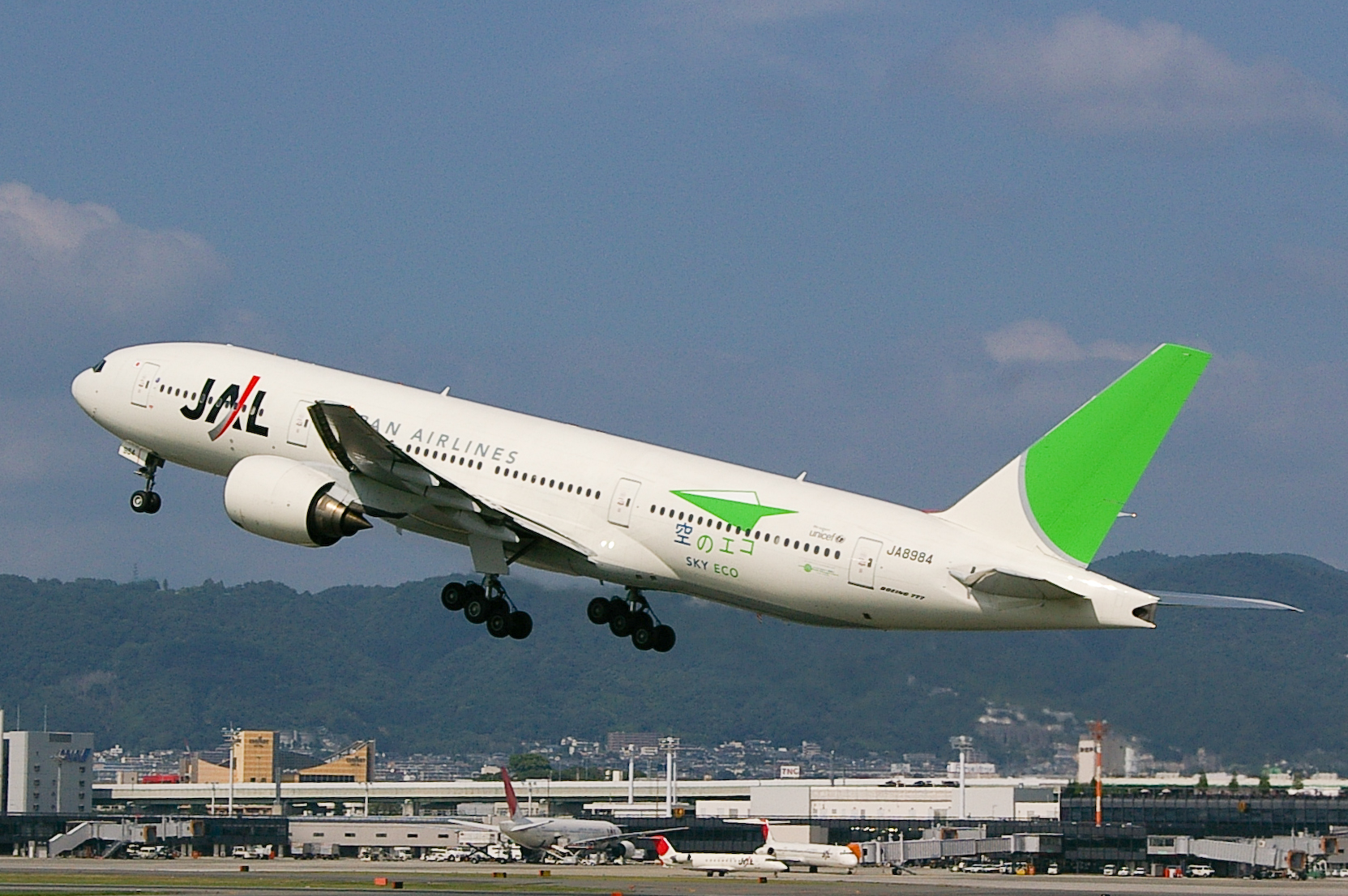 A Boeing 777–200 aircraft in mid air during take-off, with the view of Itami Airport in the background