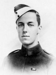 A head and shoulders portrait of a young man with dark hair in military uniform. He is wearing a cap tilted on one side of his head, and has a medal ribbon on his breast.