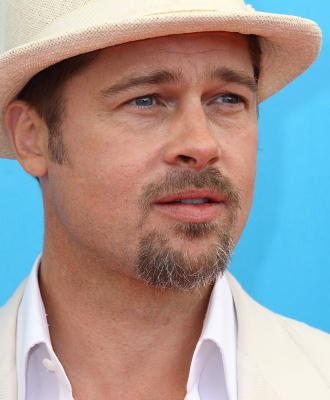 A Caucasian with light brown hair, blue eyes, and a mustache and short brown beard, in front of a turquoise background. He is wearing a white shirt and white hat.