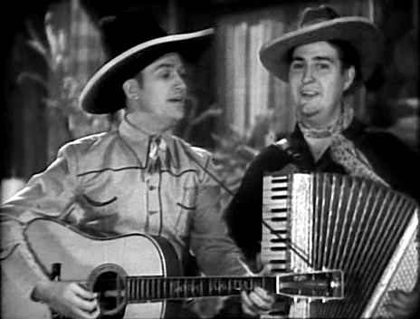 Gene Autry and Smiley Burnette singing in In Old Santa Fe film, 1934.png