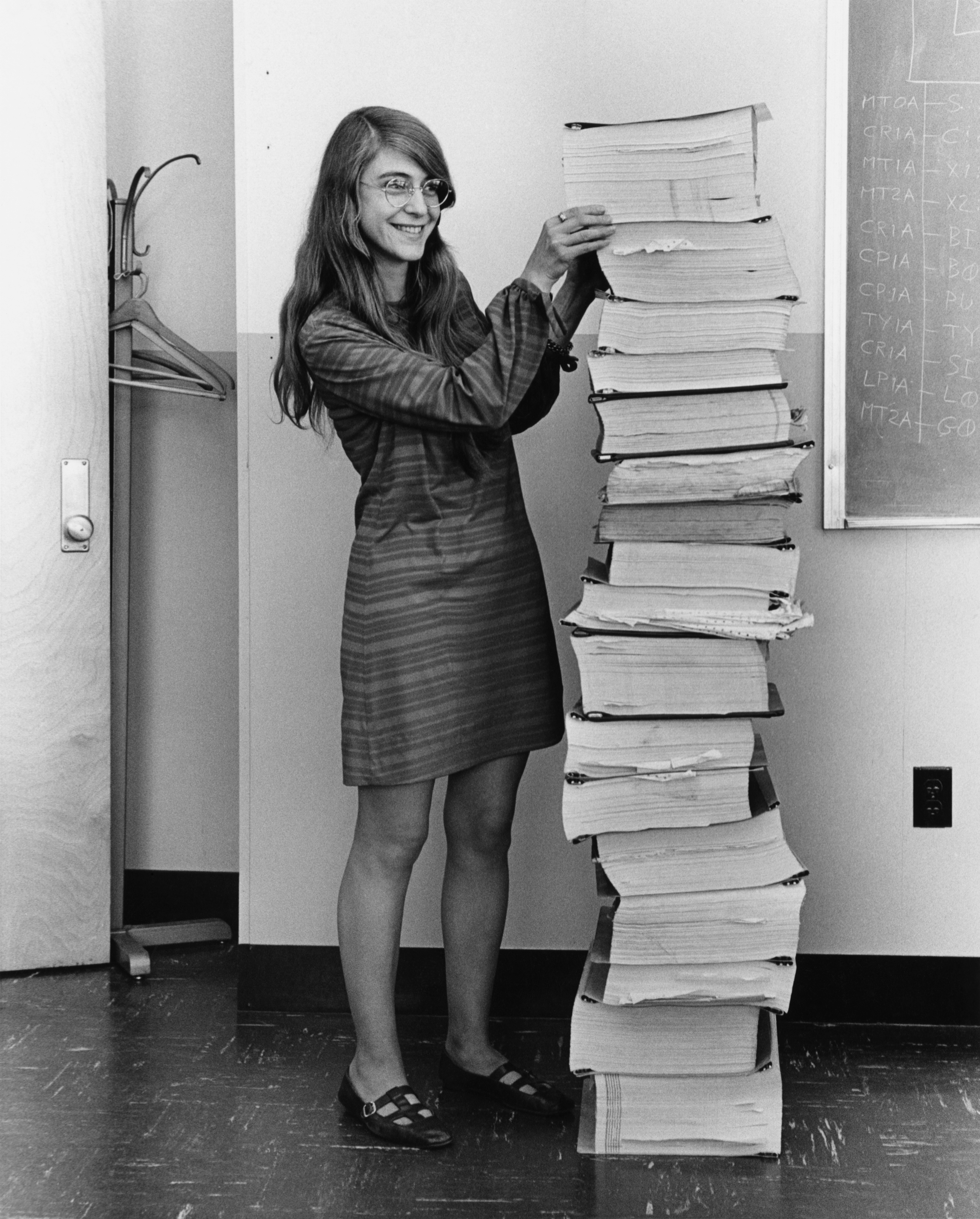 Margaret Hamilton standing next to the code for the moon landing
