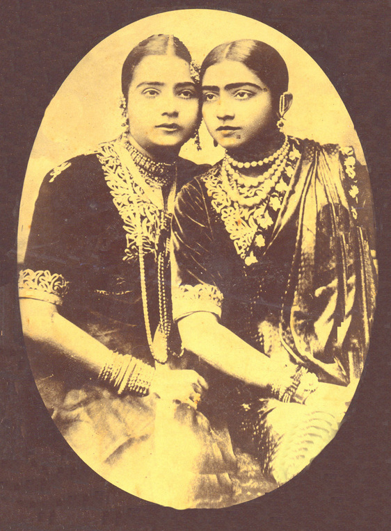 A studio photograph of two dancing girls sitting side by side