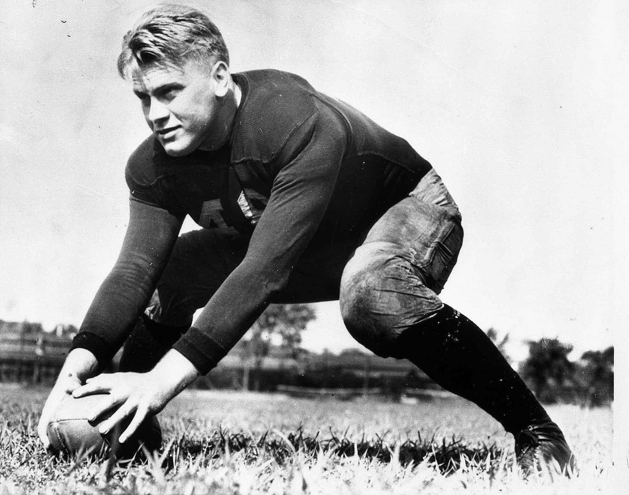 A uniformed but helmetless American Football player is shown on a football field. He is in a ready position, with legs in a wide stance and both hands on a football in front of him.