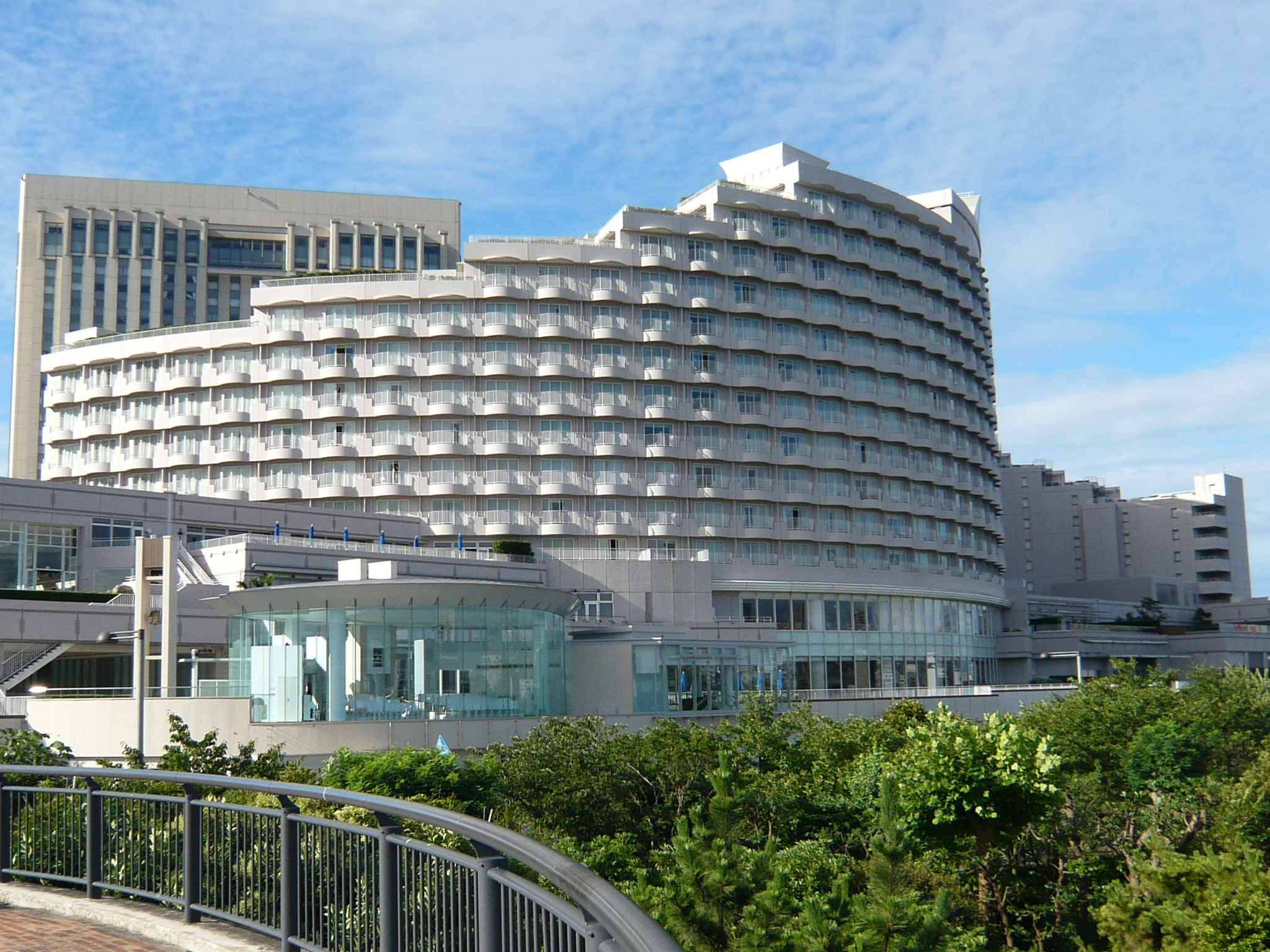 large circular multi-story building with stepped upper levels, facade consisting of multiple rows of balconies; foreground is a tree-lined park area, with a curved walkway railing, and additional buildings behind