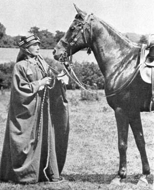 A black-and-white photograph of a European woman dressed in beduoin robes and head covering standing in front of a dark horse equipped with a bridle and saddle.