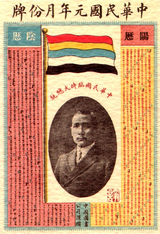 alt=A calendar with a picture of a Chinese man in the center. On top of it stands a flag with five horizontal stripes (red, yellow, blue, white and black).