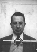 Mug shot of a man with glasses in suit and tie. The number O-15 appears in front of him.
