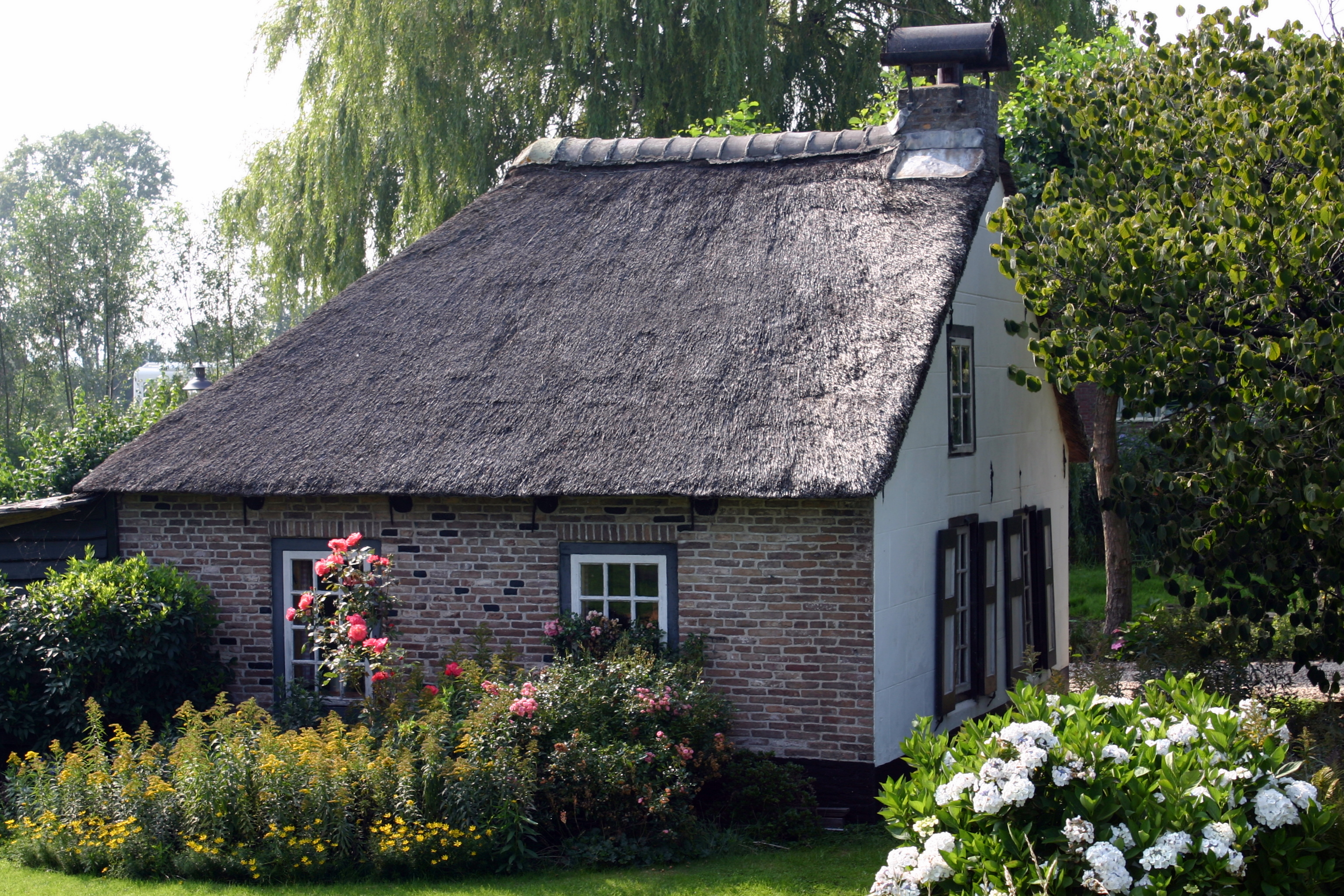 Kleine boerderij onder zadeldak met gepleisterde punt gevel waarin vensters met oude kozijnen - Oude huis gevel ...