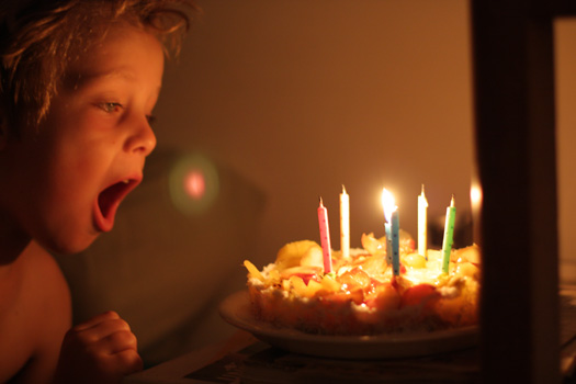 Child blowing out candles on a vegan tart (7843233606)