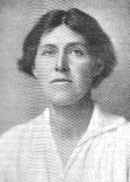 A white woman, her short dark hair center-parted, wearing a white blouse.