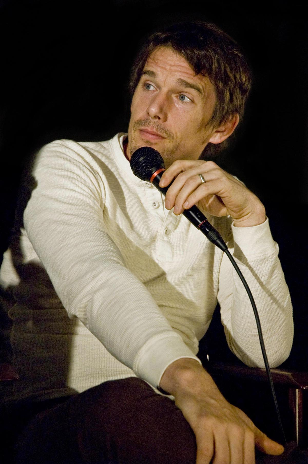 A Caucasian male with light brown hair and light brown stubble is facing to the left. He is wearing a white long sleeve shirt, and is holding a black microphone.