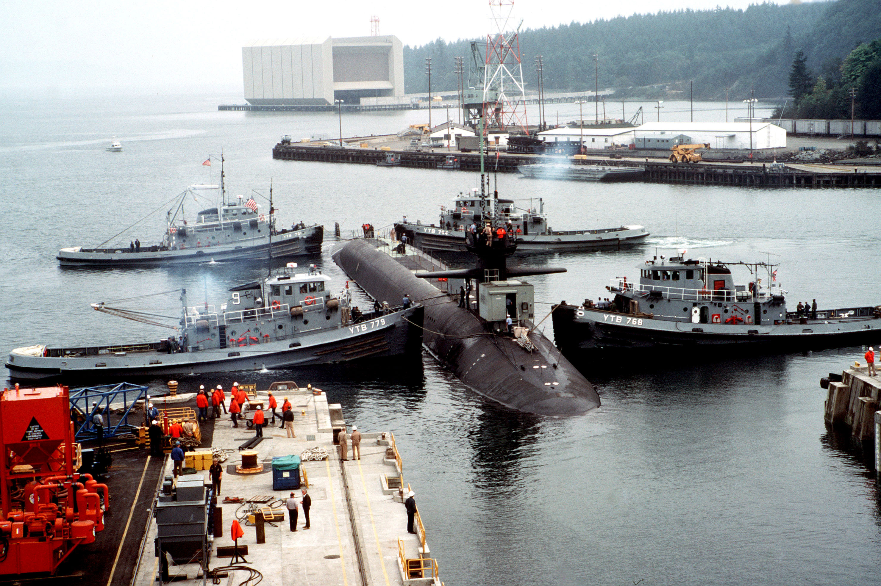 Four Natick class harbor tugs guide USS Ohio (SSBN-726) out of drydock.jpg