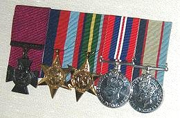 Row of five military medals with ribbons