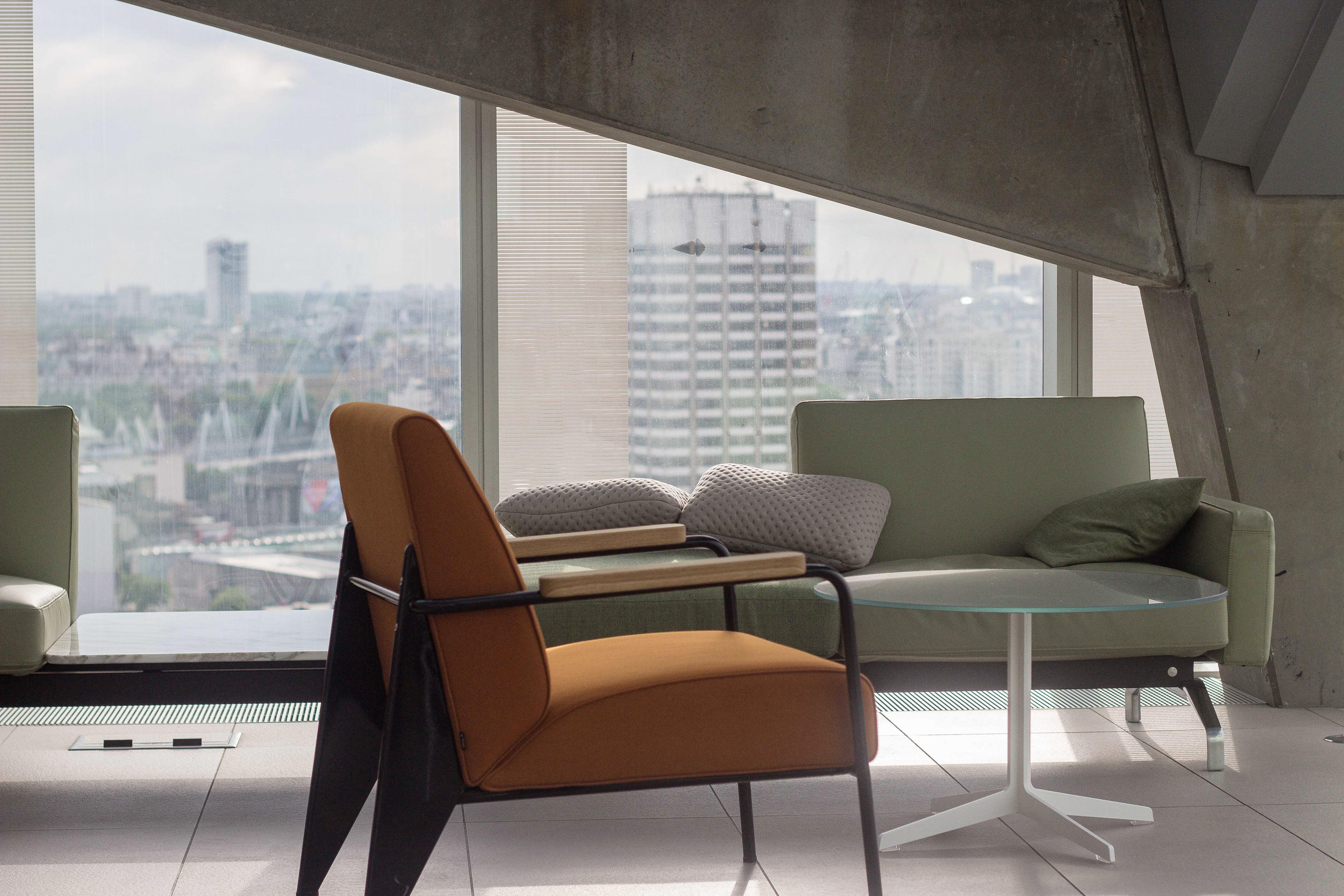 title Canto da mesa de café em um apartamento em Londres Unsplash Uma cadeira, uma mesa de café e um sofá ao lado de uma janela do chão ao teto e um armário vazio