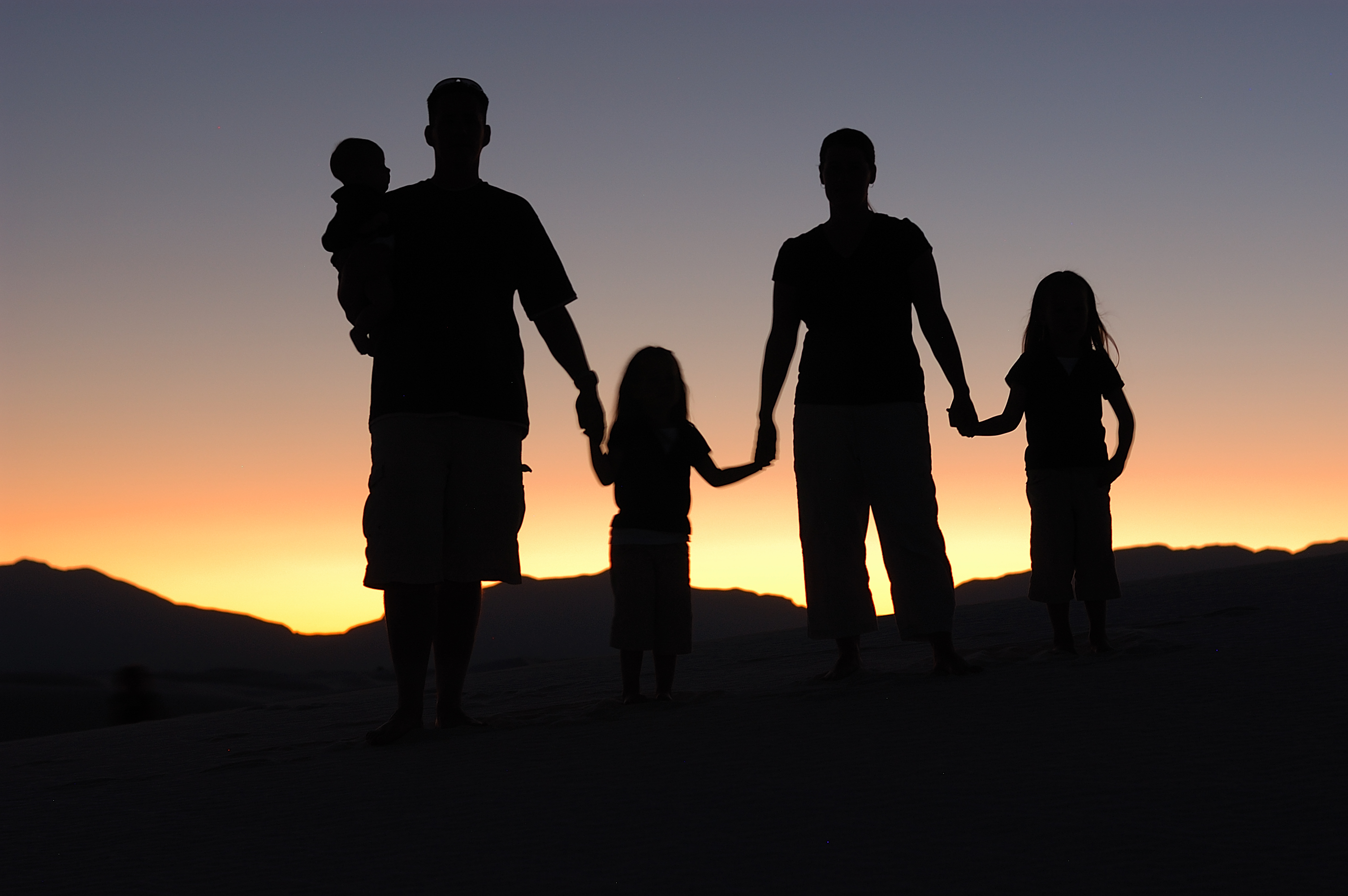 Two parents and three children silhouetted against a twilight sky