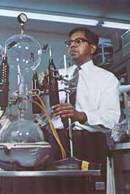 Cyril Ponnamperuma mentre esegue un esperimento presso i laboratori della NASA per testare la possibilità della vita su Giove, sull'impronta dell'esperimento di Stanley Miller. Delle scariche elettriche vengono generate in una miscela di acetilene e metano a bassissime temperature, ottenendo delle catene polimeriche.