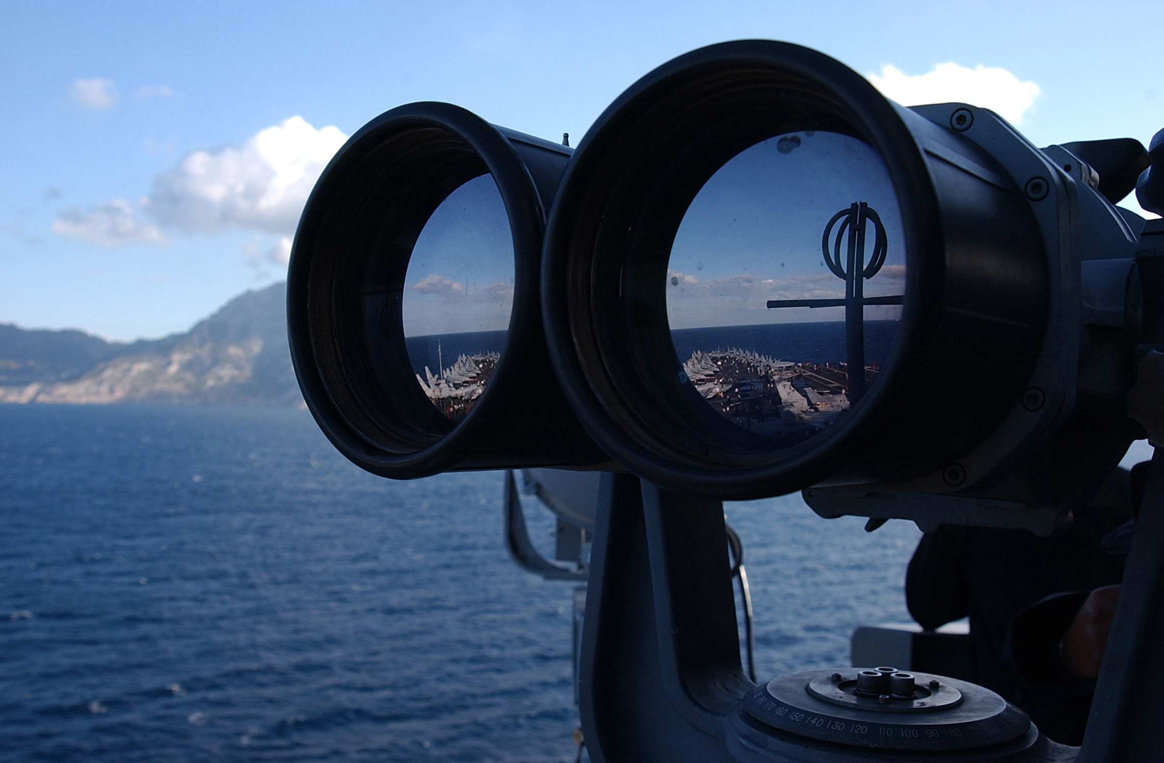 Photograph of binocular lenses from front, reflecting 2 views of an aircraft carrier