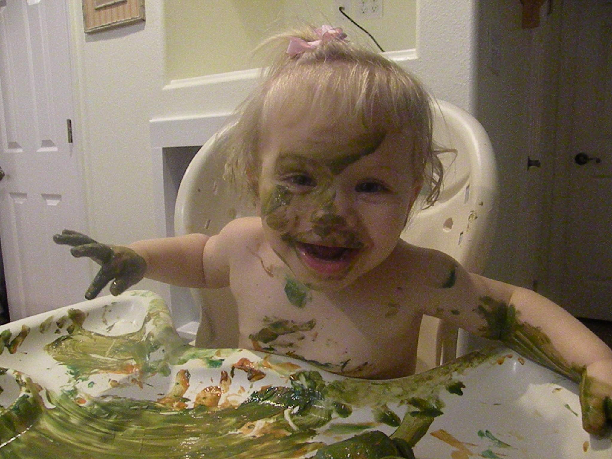 Toddler in a high chair smeared with green goop