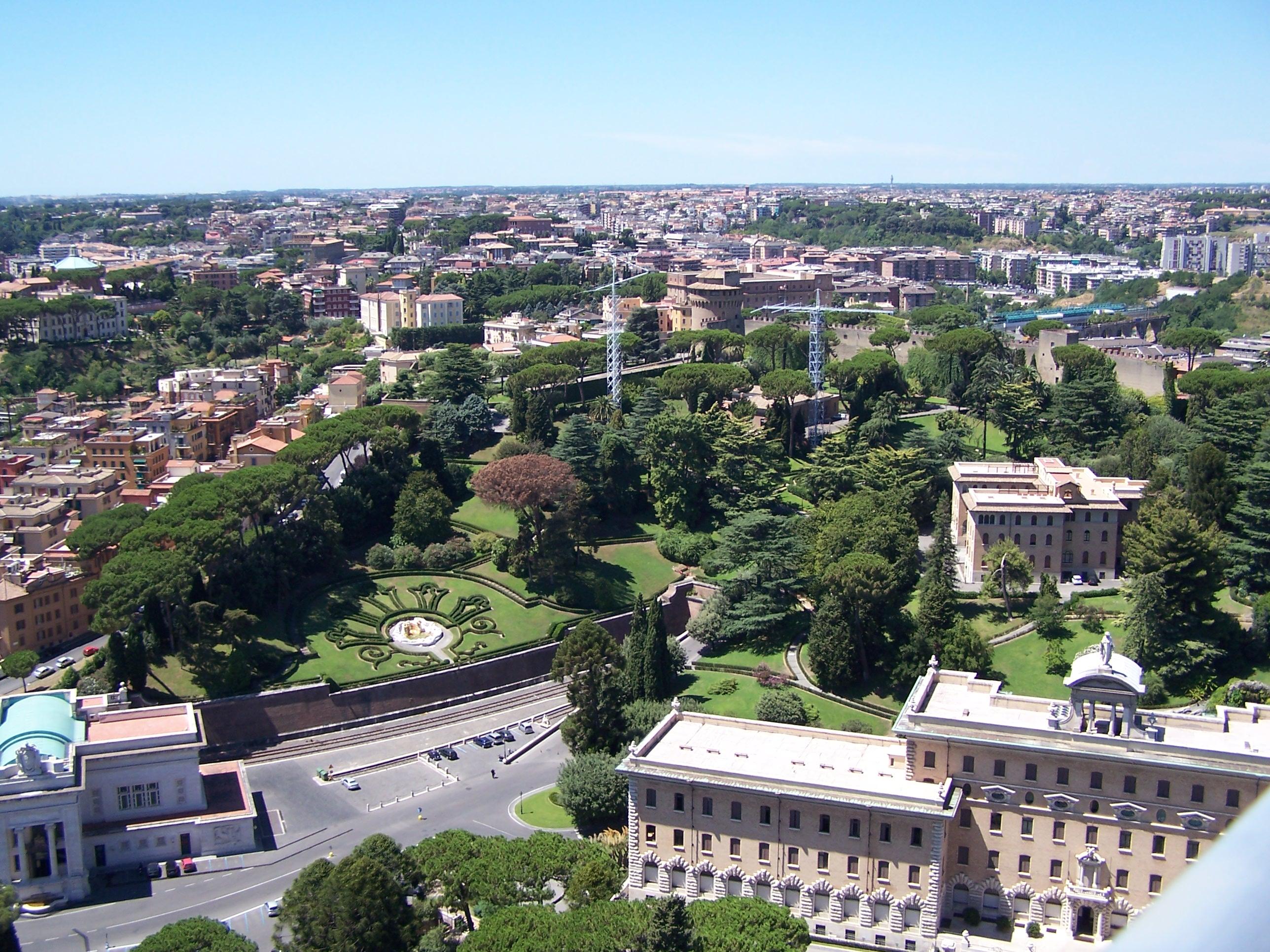 Ein Teil der Vatikanischen Gärten mit dem Bahnhof (linker Vordergrund) und dem Regierungspalast (rechter Vordergrund)