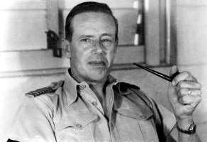 Informal portrait of man with short dark hair in light-coloured open-necked military shirt, holding a pipe