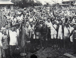 A couple hundred men are all facing the camera, smiling and cheering. Many have their hands raised. The men are wearing uniforms, t-shirts, and shorts. Huts and trees can be seen in the background.