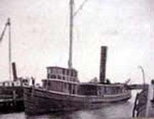 the open boat  a small steamship sits at dock mast and smokestack visible and the cabin facing front