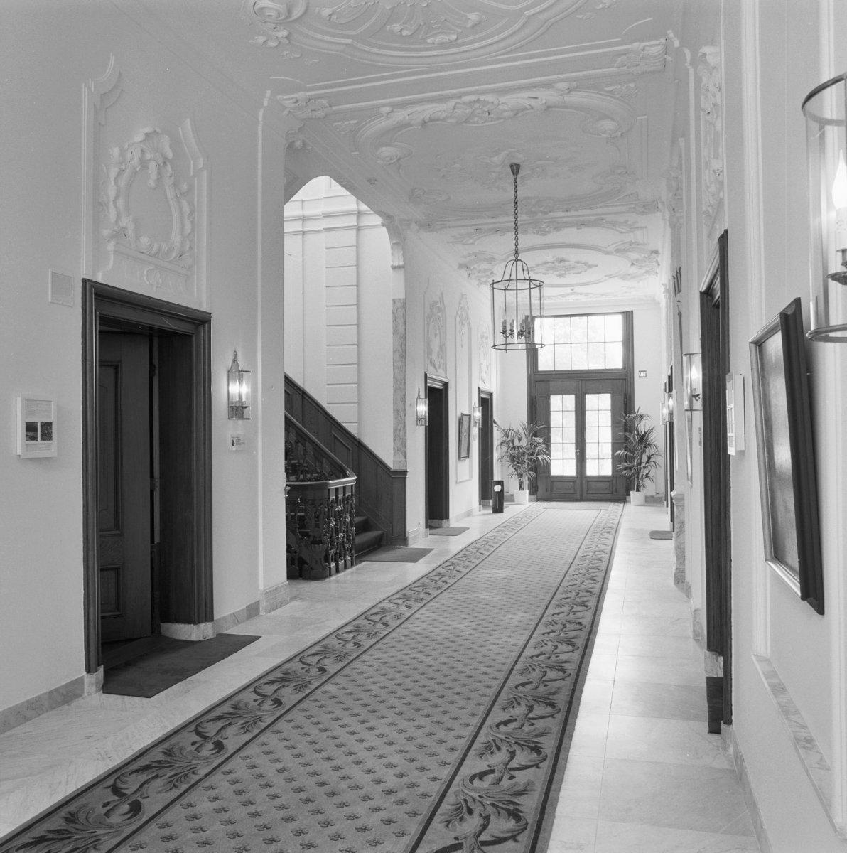 File Interieur, overzicht van de gang met stucwerk en marmeren tegels, links het trappenhuis