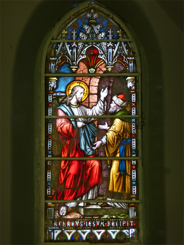 Stained glass rendition of Zacchaeus receiving Jesus into his house.