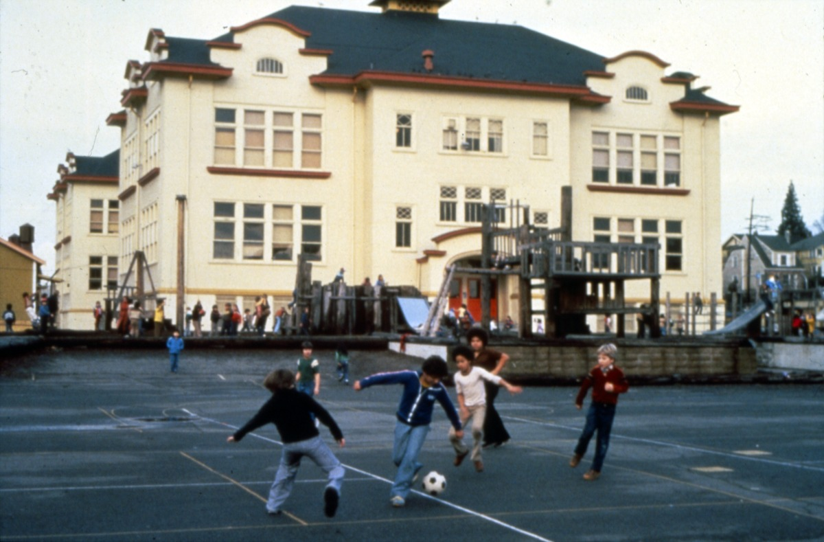 Children playing soccer in the foreground with the University Heights building in the background