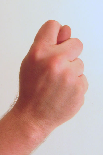 Gesture fist with thumb through fingers
