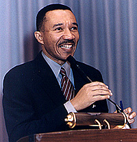 An African-American male with a mustache wearing a black suit with a light blue shirt and a red and white diagonally striped tie smiles as he stands behind a podium and adjusts a microphone with his right hand.