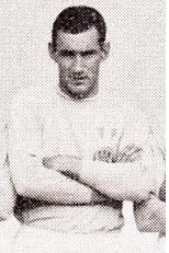 A man with short black hair, dressed in a light-coloured football shirt and light-coloured shorts, standing with his hands crossed.