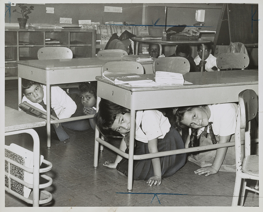 Elementary children practicing duck and cover