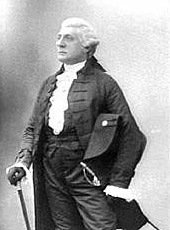Three-quarters monochrome photograph of a man facing to his right, dressed in a white wig, ruffled shirt, high-waisted trousers with sword hanging from the belt, jacket, and gloves. He rests his right hand on a walking stick, and holds a large Napoleon-style hat under his left arm.