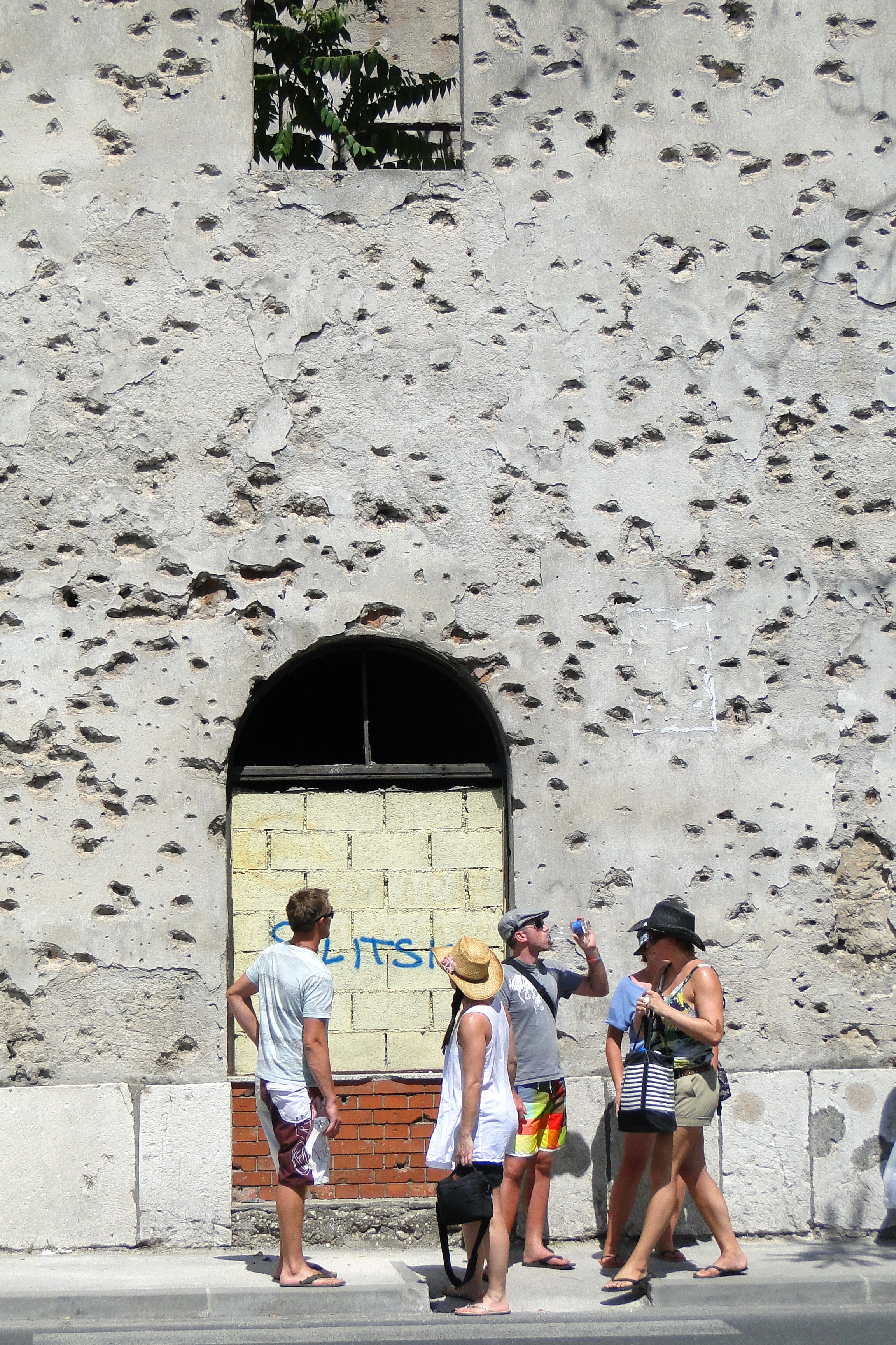 File:Visitors Stand in Front of War-Damaged Facade - Mostar - Bosnia and