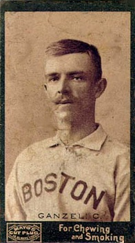 A sepia-toned photograph of a mustachioed man wearing a white baseball jersey