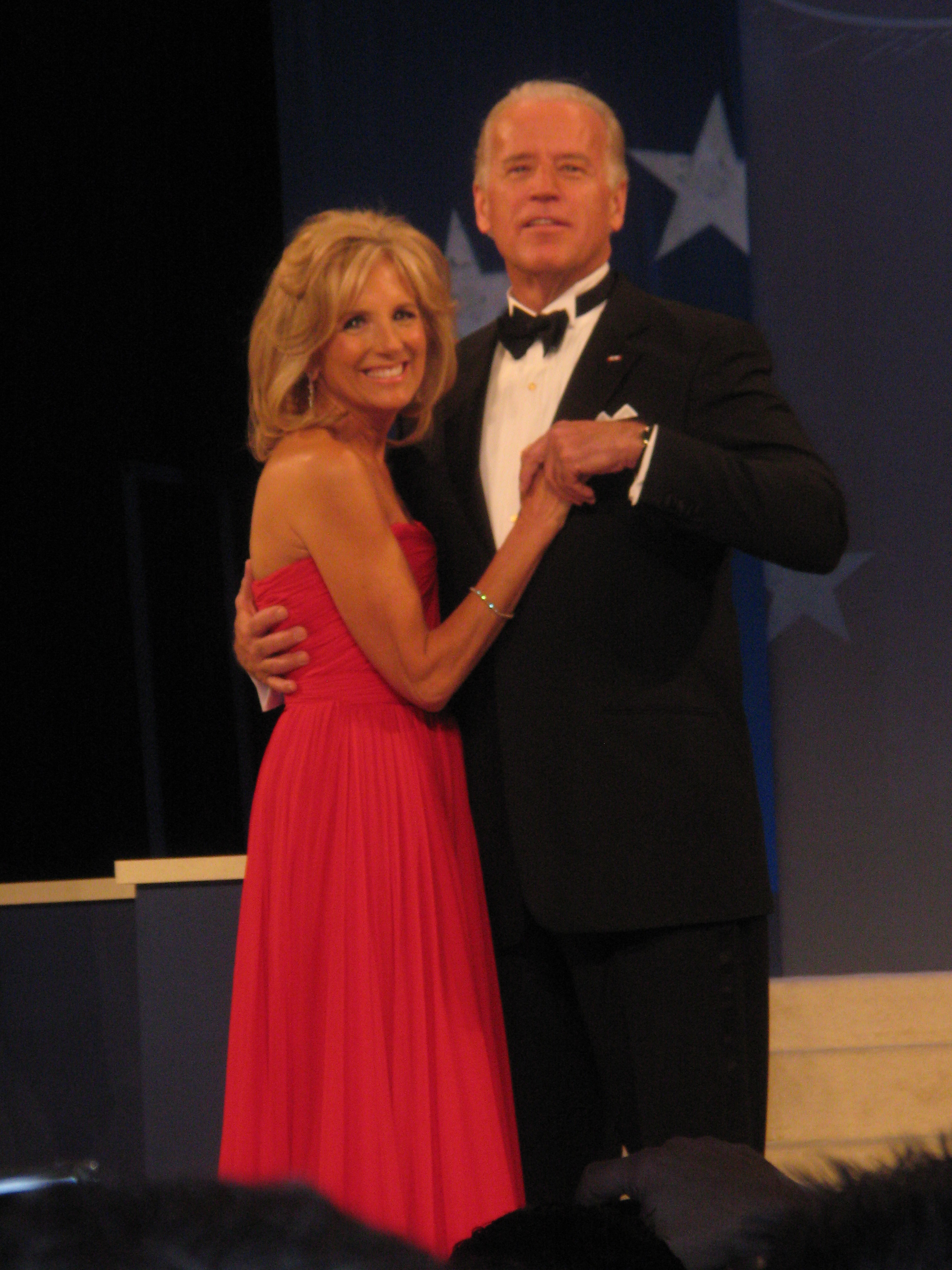 A Caucasian man in a tuxedo dances with a blonde woman in a red dress.