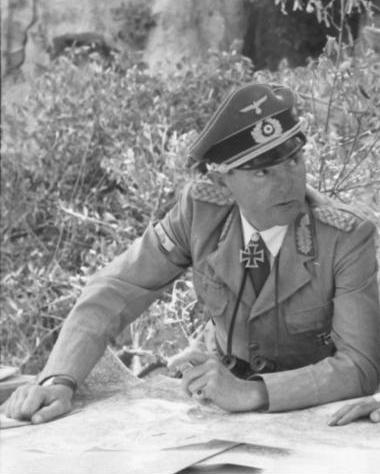 alt=A man wearing a military uniform, peaked cap, and an Iron Cross displayed at the front of his uniform collar.