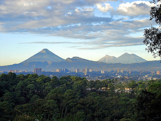"View of Guatemala City with the ""Agua"", ""Fuego"", ""Acatenango"" volcanoes in the background."