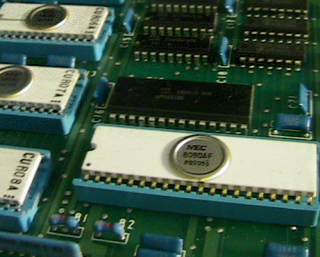 Several PDIPs and CERDIPs. The large CERDIP in the foreground is an NEC 8080AF (Intel 8080-compatible) microprocessor. Nec8080.png
